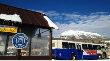 Photo of a Summit Stage bus at a bus stop in front of a mountain.