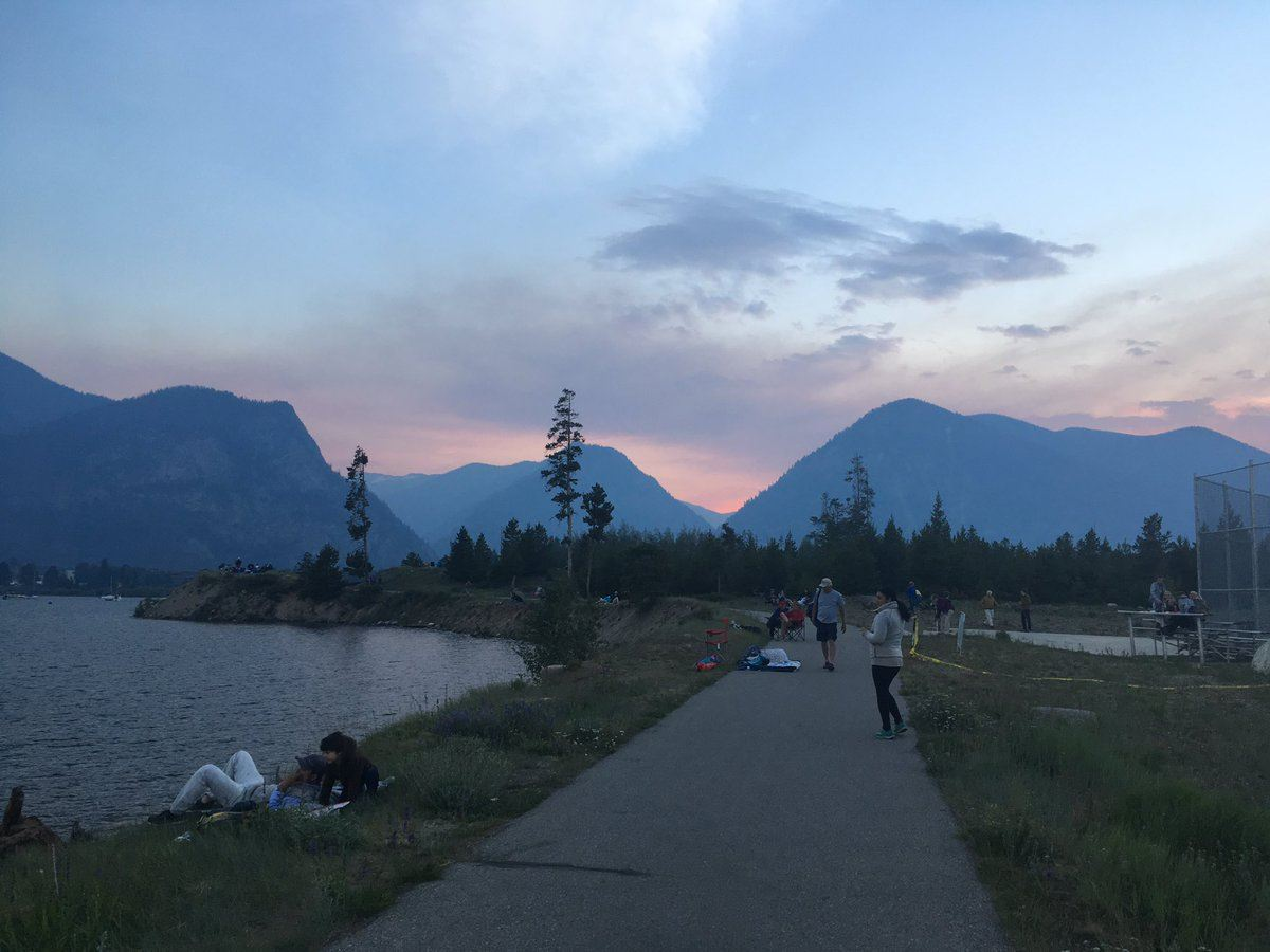 People walking along a recreational pathway. Mountains in the distance are visible, but smoke is in