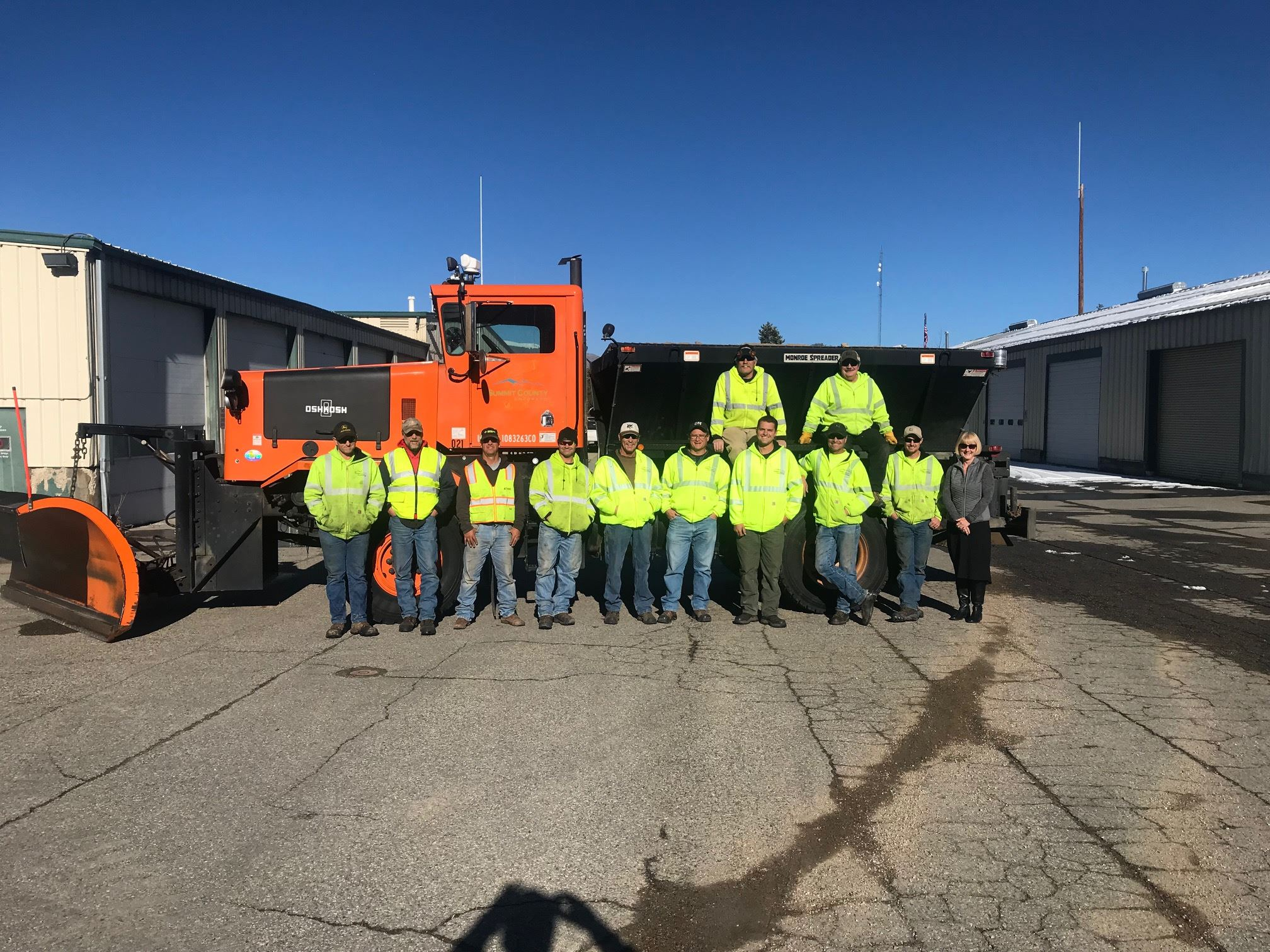 The Summit County Road and Bridge staff in front of a snowplow
