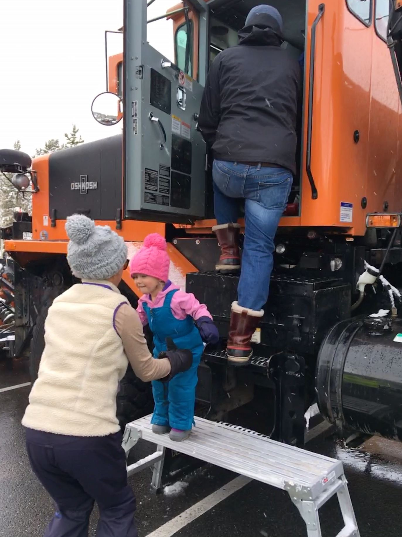 A woman helps a little girl out of a snow plow.