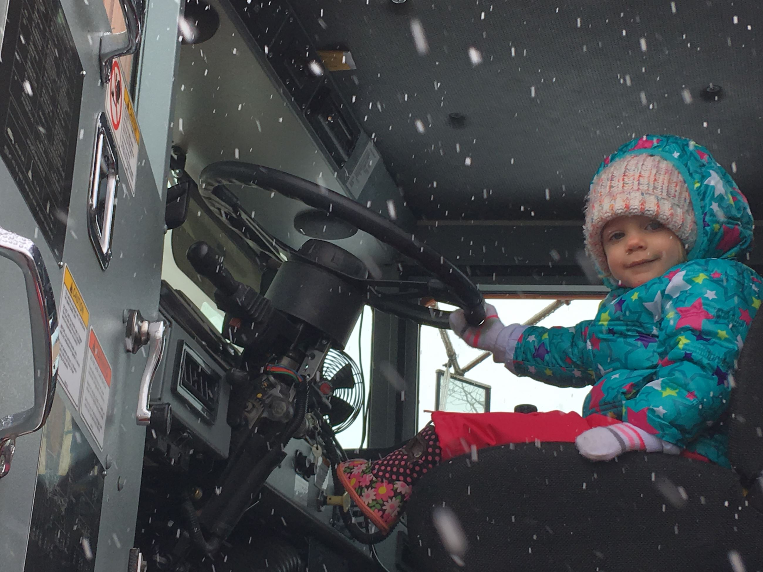 A toddler waves from the seat of a snowplow.
