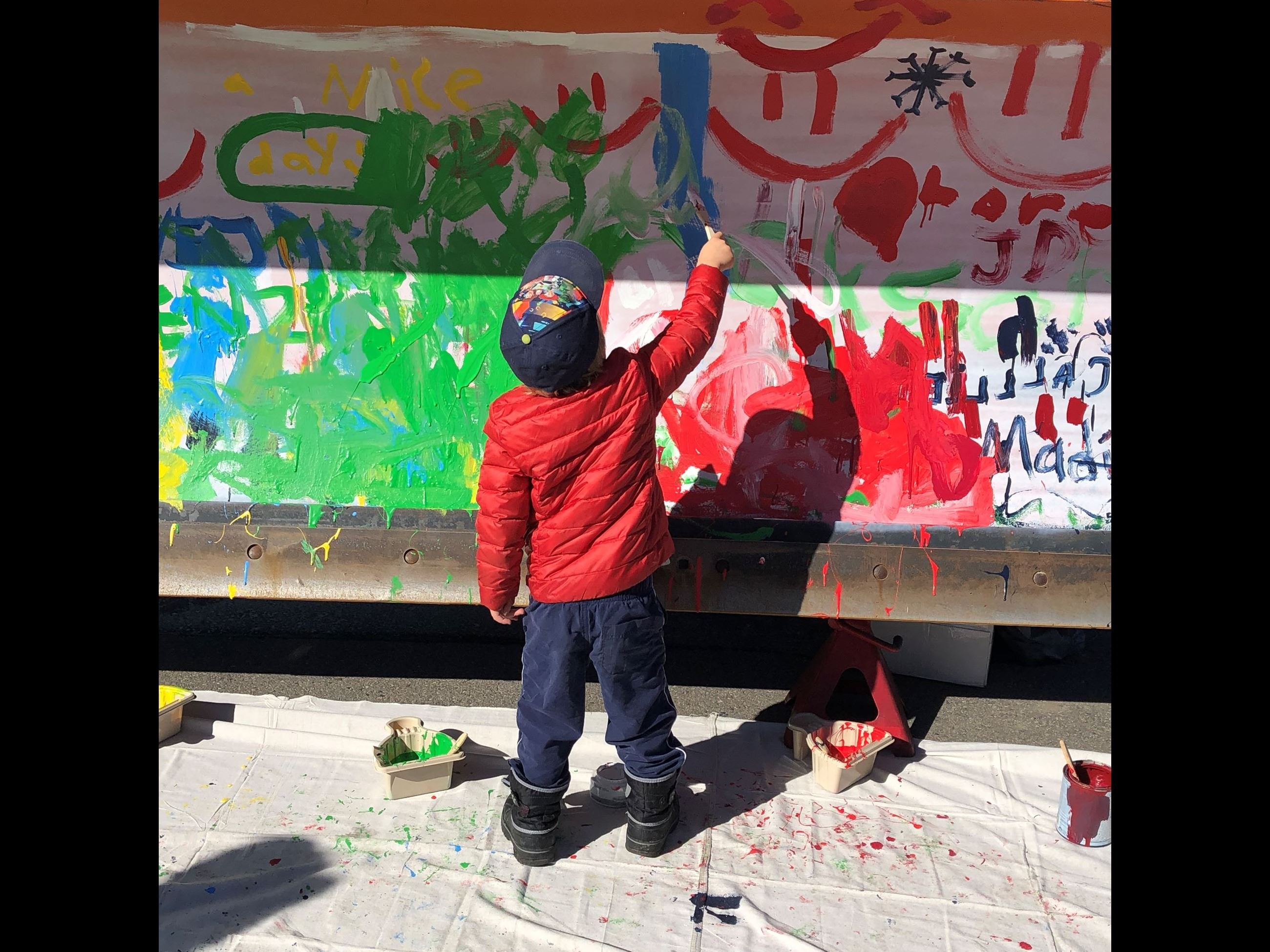 A child paints a plow blade.