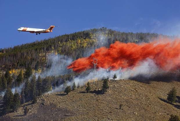 Airplane dropping fire retardant on the forest.